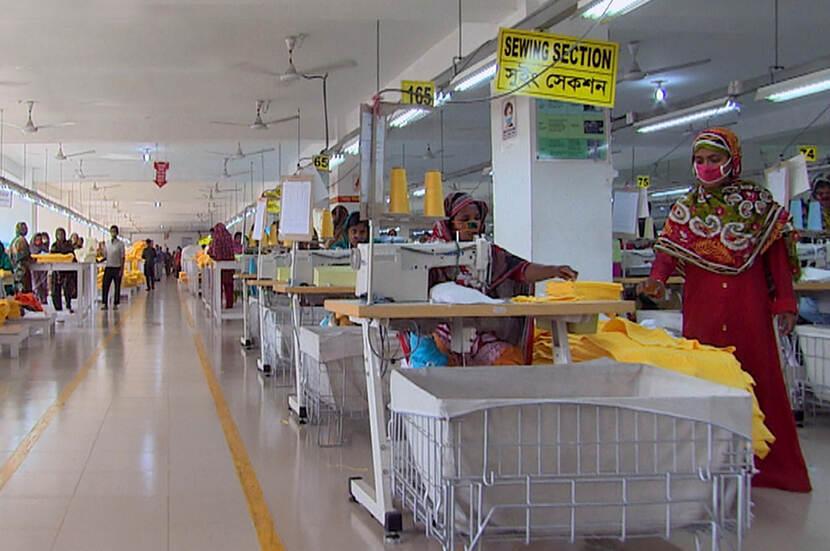 Mensen in textielfabriek met mondkapjes, naaimachines en bakken textiel