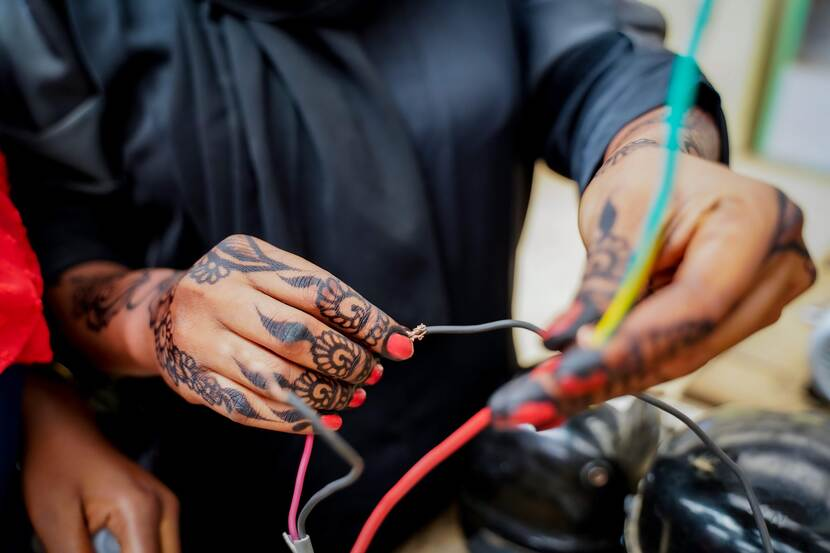 Beschilderde vrouwenhanden houden electrische draden vast